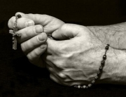 Hands praying the rosary