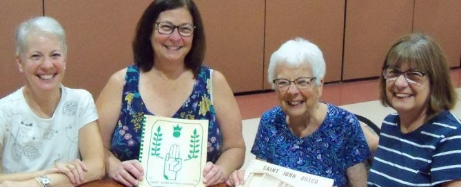 Left to right:  Sue Shanks, Diane Schneider, Mary Lauritz, and Lynne Hall with SJB School Yearbooks